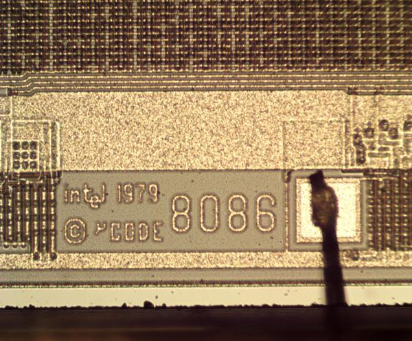 Under the microscope, the 8086 part number is visible as well as the copyright date. A bond wire is connected to a pad. Part of the microcode ROM is at the top.