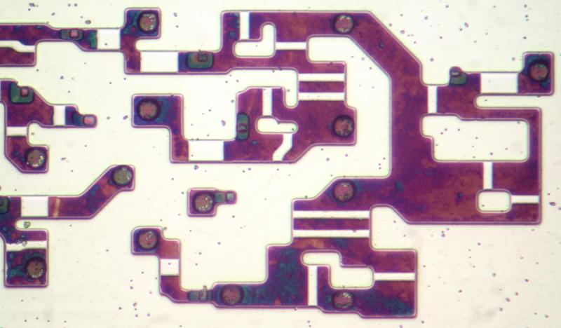 Closeup of some transistors in the 8086. The metal and polysilicon layers have been removed in this photo. The doped silicon has a dark purple appearance due to thin-film interference.